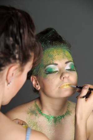 artist's model: Model getting some vivid make-up applied before a fashion photoshoot