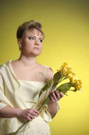 the woman in a yellow dress with flowers in hands Stock Photo - 13218887