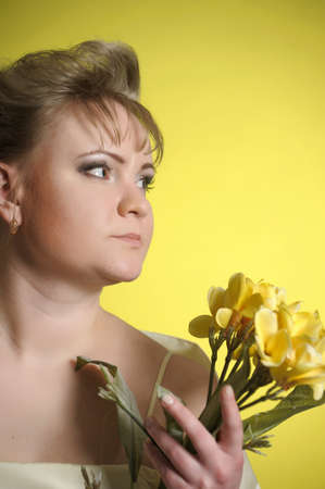 the woman in a yellow dress with flowers in hands Stock Photo - 13218892