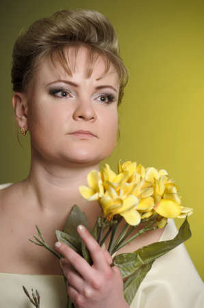 the woman in a yellow dress with flowers in hands photo