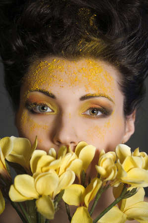 The beautiful young woman with a creative yellow make-up and flowers Stock Photo - 13191739
