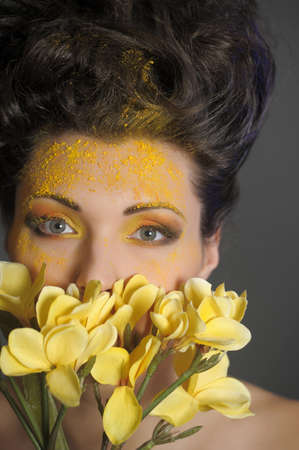 The beautiful young woman with a creative yellow make-up and flowers Stock Photo - 13191734