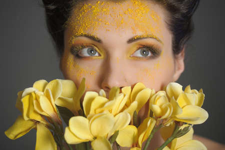 The beautiful young woman with a creative yellow make-up and flowers photo