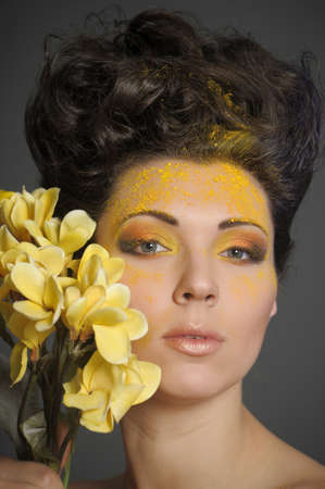 The beautiful young woman with a creative yellow make-up and flowers Stock Photo - 13133706