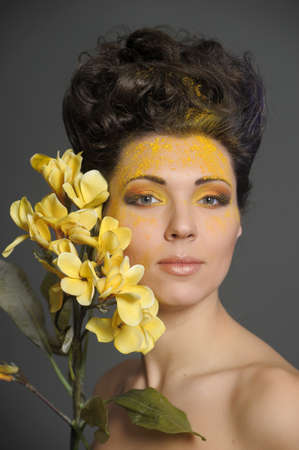 The beautiful young woman with a creative yellow make-up and flowers Stock Photo - 13133703
