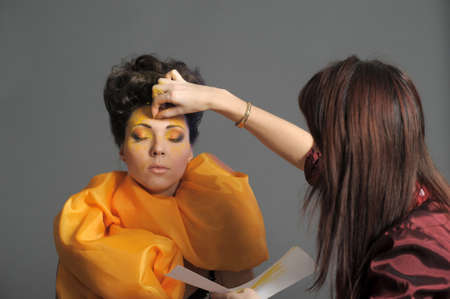 Model getting some vivid make-up applied before a fashion photoshoot  photo