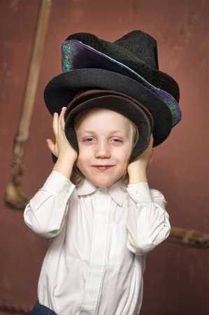 the boy measures at once many hats Stock Photo - 13443494