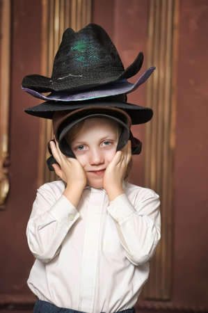 the boy measures at once many hats Stock Photo - 13443486