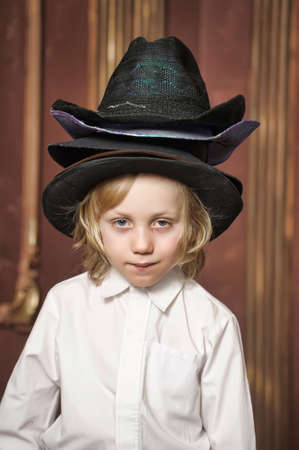 the boy measures at once many hats Stock Photo - 13443501