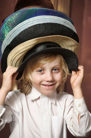 the boy measures at once many hats Stock Photo - 13443670