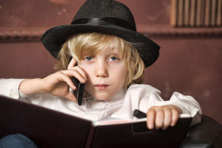 boy in a hat with a mobile phone and a book photo