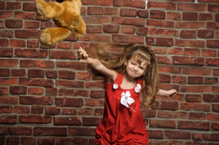 the little girl throws a toy bear photo
