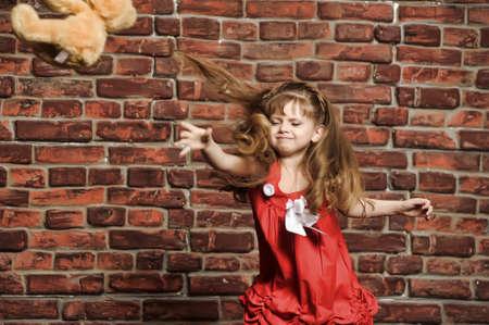 long shots: la bambina lancia un orso giocattolo