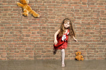 angry teddy: the little girl throws a toy bear Stock Photo
