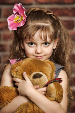 portrait of a girl with a flower in her hair and bear in hand photo