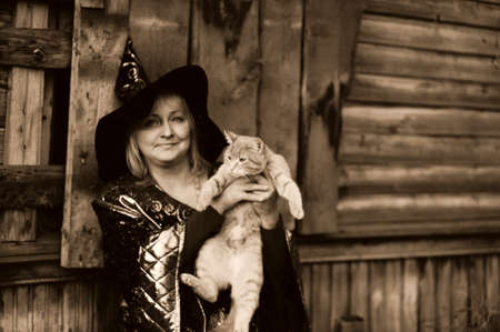 magick: Witch with a cat in her arms Stock Photo