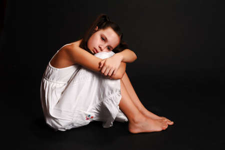 discouraged: The girl the teenager in depression on a black background