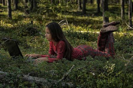 educacion gratis: ni�a con ordenador port�til en el bosque