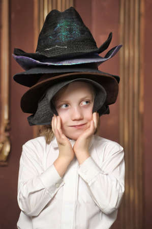 the boy measures at once many hats Stock Photo - 13480687