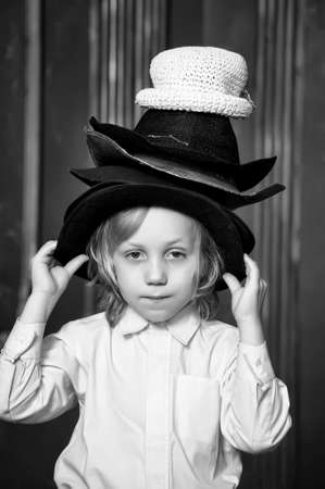 the boy measures at once many hats Stock Photo - 13480747