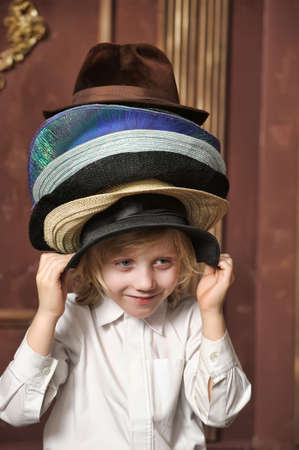 the boy measures at once many hats Stock Photo - 13480789