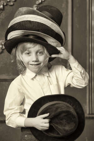 the boy measures at once many hats Stock Photo - 13480811