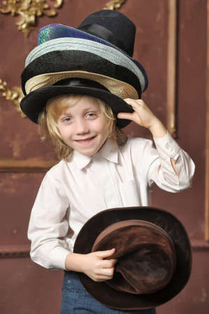 the boy measures at once many hats Stock Photo - 13480690