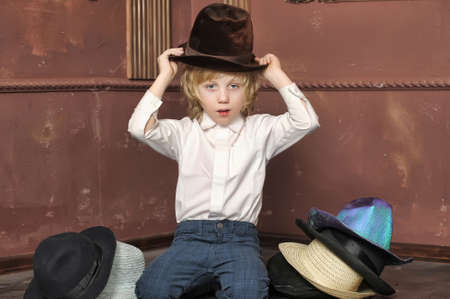 the boy measures at once many hats Stock Photo - 13480758