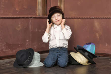the boy measures at once many hats Stock Photo - 13480782