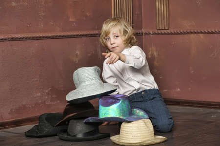 the boy measures at once many hats Stock Photo - 13549054