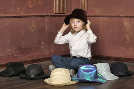 the boy measures at once many hats Stock Photo - 13499031