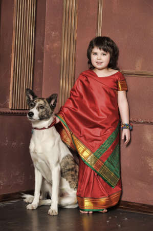 indian style sitting: little girl in the national Indian suit with a dog Stock Photo