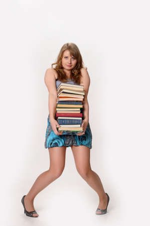Woman carrying a heavy stack of books photo