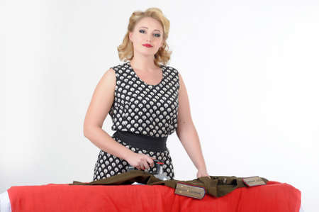 the young girl irons a soldier s blouse Stock Photo - 13526547