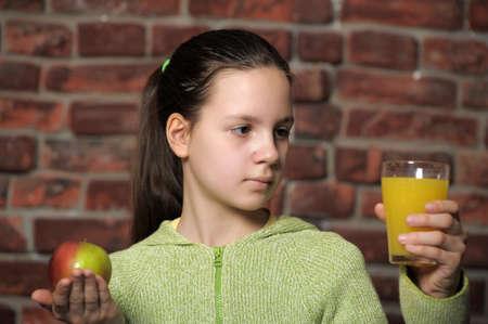 teen girl with an apple and orange juice  photo