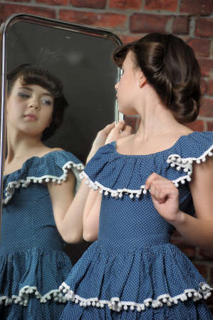 the girl admires itself in a mirror Stock Photo - 13684027