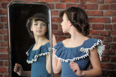 the girl admires itself in a mirror photo