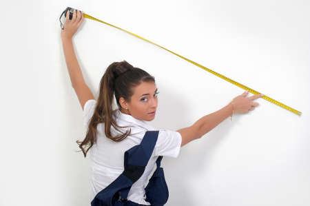 metering: Young woman with tool belt is holding a metering rule
