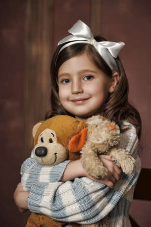 girl on an old suitcase with a toy bear  photo