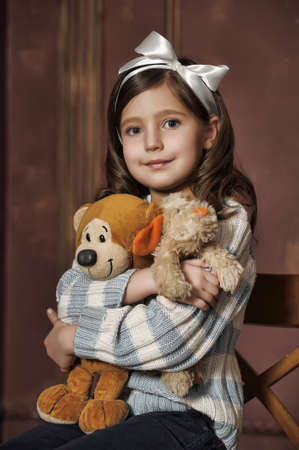 favorite colour: girl on an old suitcase with a toy bear  Stock Photo