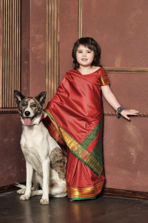 house trained: little girl in the national Indian suit with a dog Stock Photo