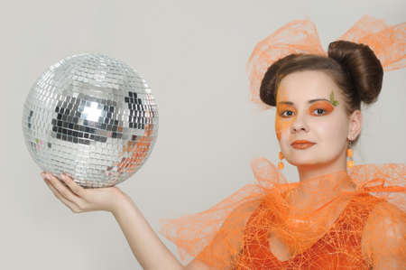 the girl with an orange creative make-up with a mirror sphere Stock fotó