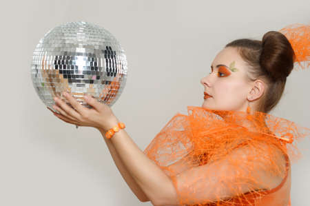 the girl with an orange creative make-up with a mirror sphere photo