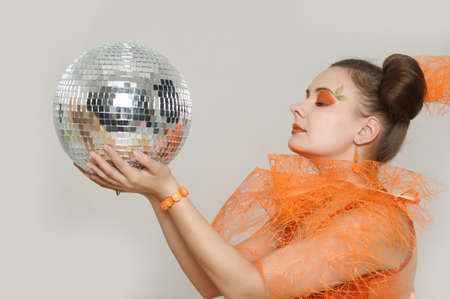 the girl with an orange creative make-up with a mirror sphere Stock Photo - 13682702