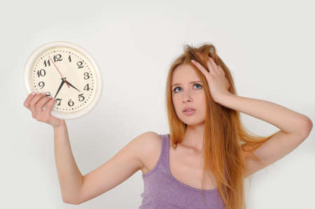 Young woman holding a clock photo
