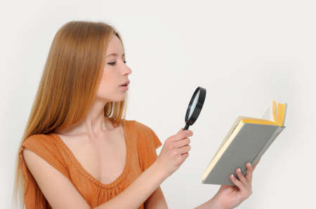 Portrait of surprised girl looking at the with book with loop Stock Photo - 13679541