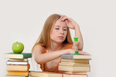 girl student with books, apple and sand-glasses Stock Photo - 13664030