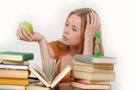 girl student with books, apple and sand-glasses photo