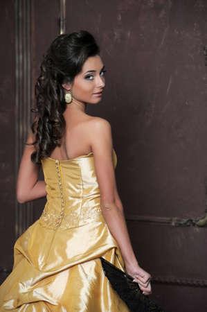 Красивая девушка в золотом платье Фото со стока