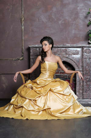 Elegant  beauty posing in a golden dress Stock Photo - 13837725